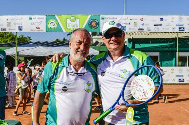 Dois homens com roupas e e raquete de tênis em um evento beneficente com patrocínio da Crédito Real.