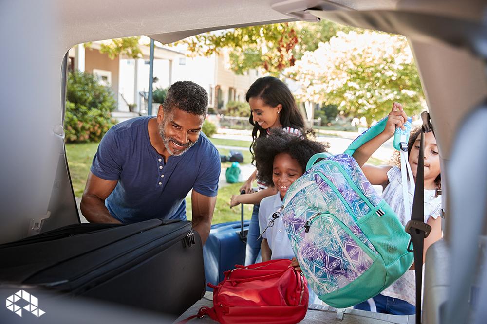 família composta por um homem e duas crianças colocando mochilas e malas no porta malas de um carro para ir viajar.